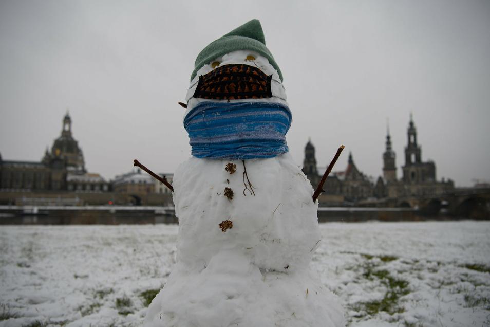 Coronakonform:: Ein Schneemann mit Mundschutz steht am Elbufer vor der Frauenkirche.