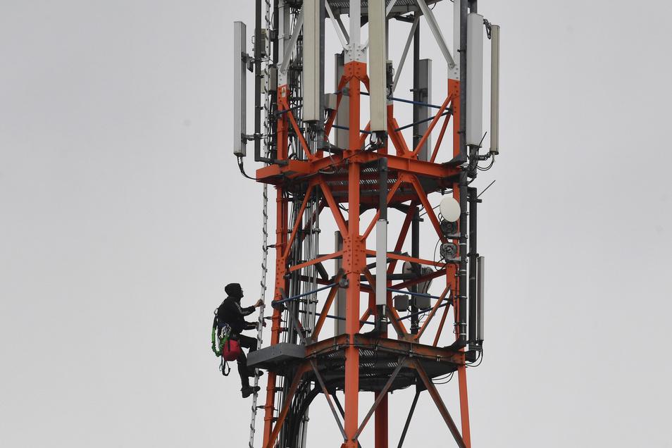 Ein Techniker klettert auf einen Funkmasten für 5G. Diesen Anblick wollen einige Coswiger in ihrer Region verhindern.