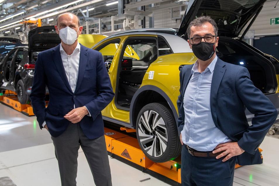 Cem Özdemir (r, Bündnis 90/Die Grünen), Vorsitzender des Verkehrsausschusses im Deutschen Bundestag, und Ralf Brandstätter, Markenvorstand Volkswagen, unterhalten sich an der Montagelinie für die vollelektrischen Fahrzeuge ID.3 und ID.4 im Werk von Volksw