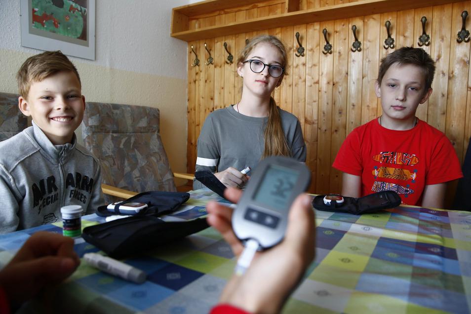 Roman, Natascha und Arseni (v.l.n.r.) messen beim Tschernobylverein in Kamenz ihren Zuckerspiegel. Er ist in Ordnung, zum Glück!