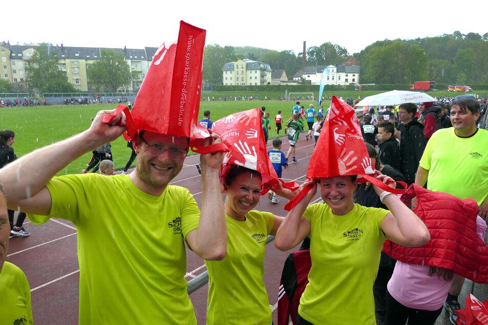 Matthias, Linda und Christiane (von links) funktionierten die Verpflegungstüten kurzerhand zu Regenmützen um.