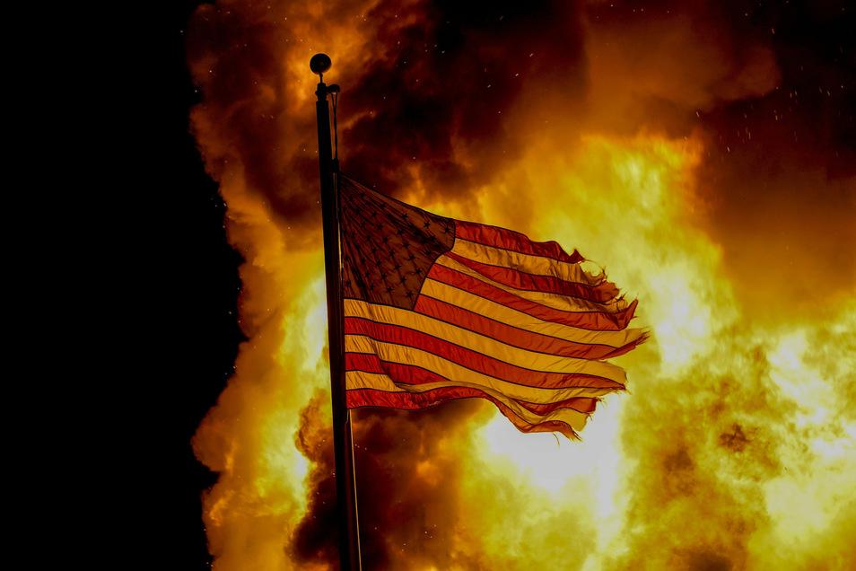 Eine US-Flagge weht über einem Gebäude der Strafvollzugsanstalt, das während der Proteste in Brand stand. Schüsse in den Rücken eines Schwarzen bei einem Polizeieinsatz im US-Bundesstaat Wisconsin haben Entsetzen und Protest ausgelöst.