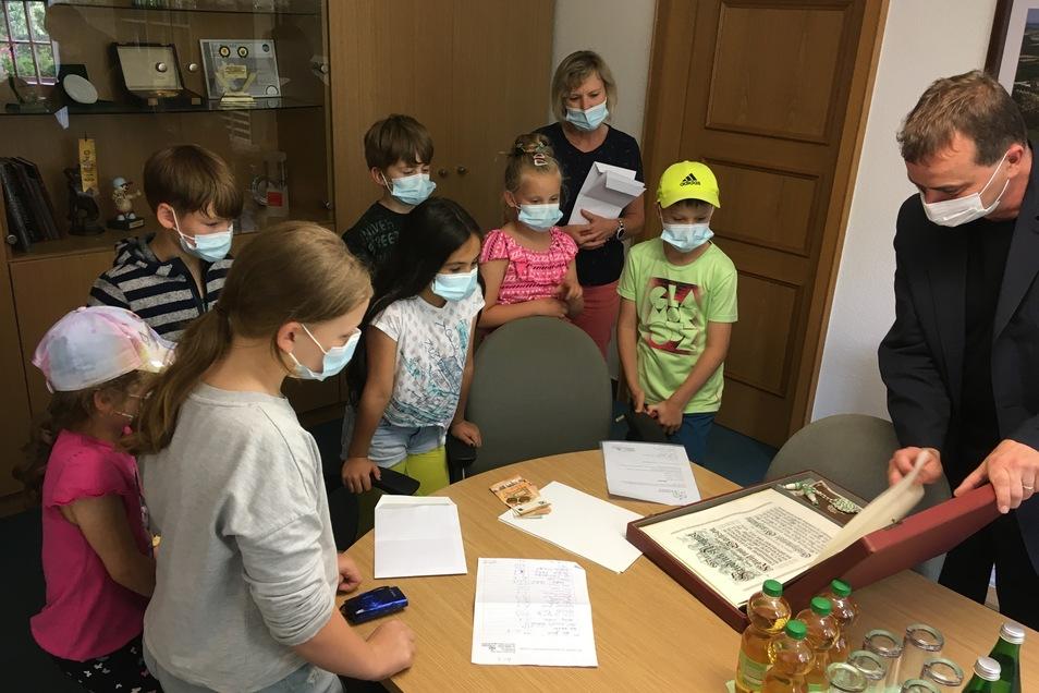 Nach dem Empfang der Spende für die Hochwasseropfer in Rheinland-Pfalz zeigte der amtierende Bürgermeister Uwe Ahrendt (Grüne) den Hortkindern das Wappenbuch der Stadt Glashütte.