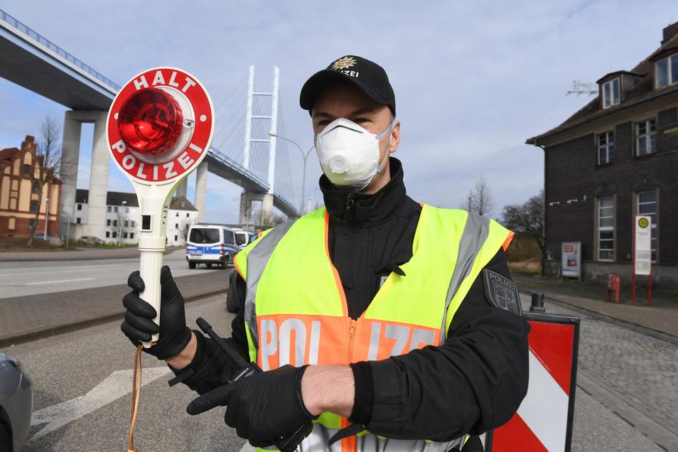 Fremde nicht erwünscht: Ein Polizeibeamter kontrolliert vor der Ziegelgrabenbrücke den Verkehr in Richtung der Insel Rügen.
