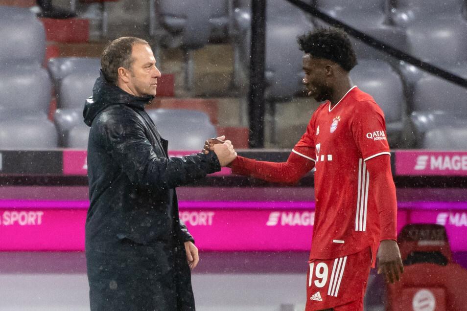 Alphonso Davies (r) und Trainer Hansi Flick von München klatschen sich nach dem Spiel ab.