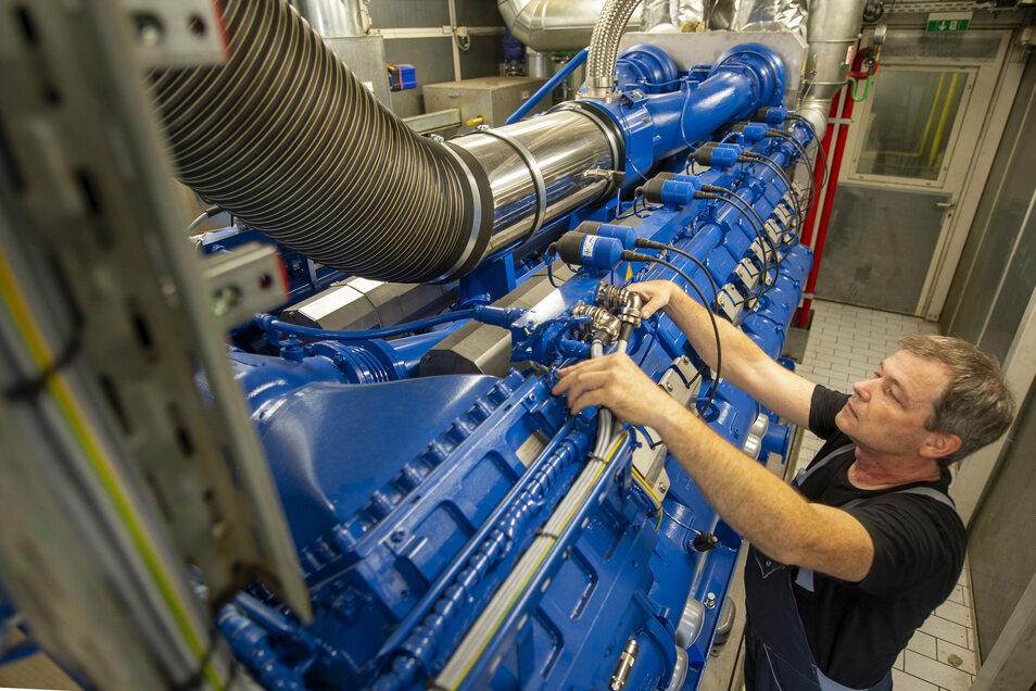 Andre Voigtländer von der Firma SES Energiesysteme GmbH schließt Steuerkabel an einen der beiden neuen Motoren im Blockheizkraftwerk Coswig an. Die Motoren erzeugen Strom und Wärme für drei Wohngebiete.