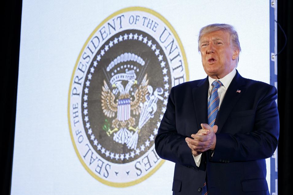 Trump vor einer verfälschten Version des offiziellen Präsidentensiegels. Unbekannte haben statt dem Original eine Fälschung an die Wand projiziert, bei der ein Doppelkopfadler zu sehen ist, der Geldscheine und Golfschläger in den Klauen hält.