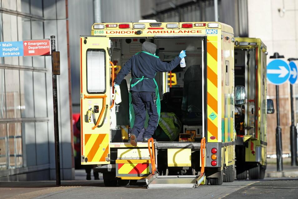 """Ein Arbeiter in Schutzkleidung desinfiziert die Rückseite eines Krankenwagens, nachdem in dem Krankenwagen ein Patient zum Krankenhaus """"Royal London Hospital"""" gefahren wurde."""