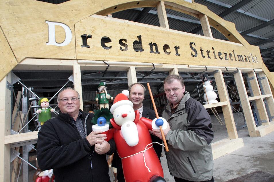 Im Jahr 2009 wurde der Striezelmarkt umgestaltet. Die Firma Erzgebirgische Holzkunst GmbH aus Oederan fertigte dazu den größten begehbaren Schwibbogen der Welt. Er ziert seitdem den Eingang zum Markt. Im Bild: Bürgermeister Dirk Hilbert (Mitte) und die be