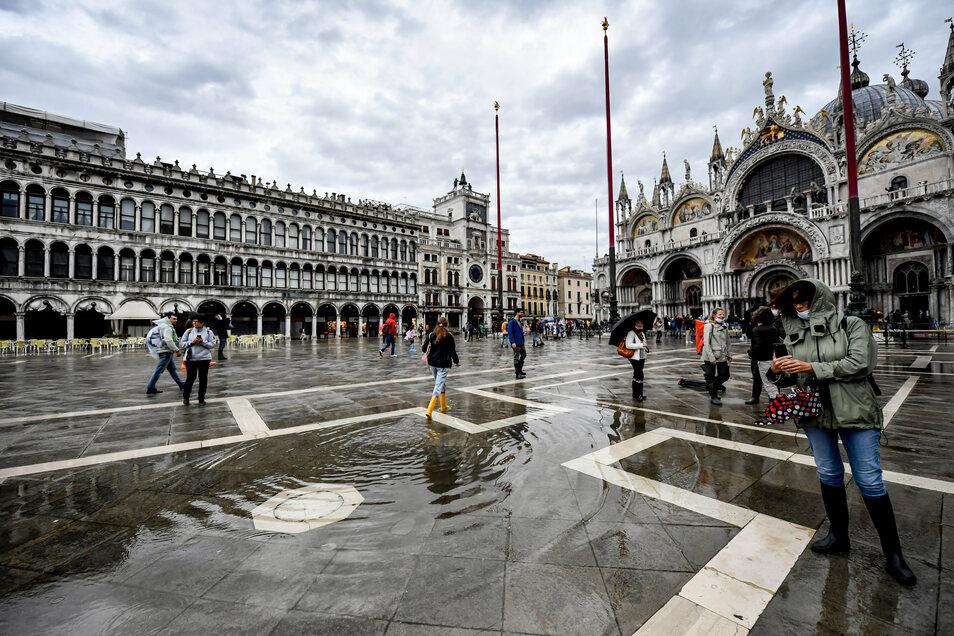 Passanten gehen bei Regen über den überschwemmten Markusplatz in Venedig. Ein Unwetter mit Regen und Sturm hat im Norden des Landes heftige Schäden angerichtet.