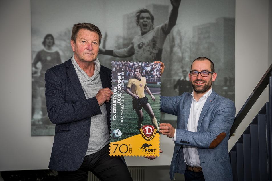 """""""Dixie"""" Dörner (l.) zeigt mit Alexander Hesse, Marketingleiter bei PostModern, ein überdimensionales Exemplar der Sonderbriefmarke."""