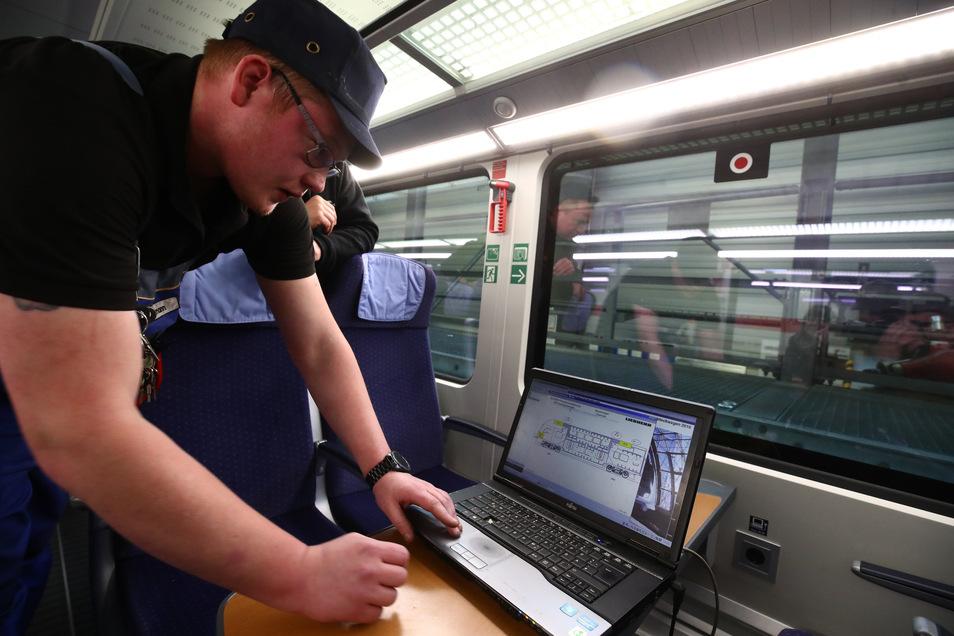 Markus Aßmann überprüft an einem Laptop die Heizungsanlage in einem IC Zug im ICE Werk Leipzig bei der Inspektion und Wintervorbereitung.