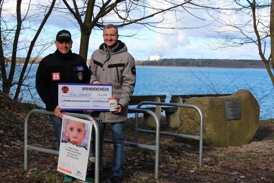 Vor dem Scheibe-Gedenkstein am Scheibe-See, wo im Oktober der Feuerwehrspendenmarsch vorbeiführen wird, überreichte Lohsas Bürgermeister Thomas Leberecht an Organisator Harald Skopi aus Nardt einen symbolischen Scheck.