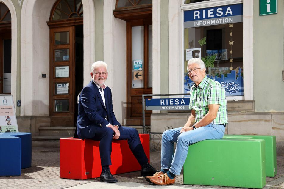 Unverkennbar: Auf den bunten Buchstaben, die zusammen das Wort Riesa bilden, sitzen Andree Schittko (l.) und Kurt Hähnichen vom Gewerbeverein HGV. Der betreibt die Riesa-Information, die jetzt 15 Jahre alt wird.