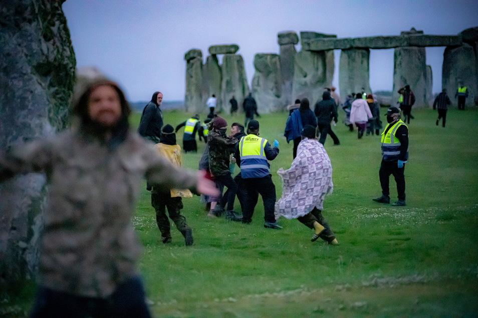Menschen springen über einen Zaun und bahnen sich ihren Weg an Sicherheitspersonal vorbei in Richtung Stonehenge.