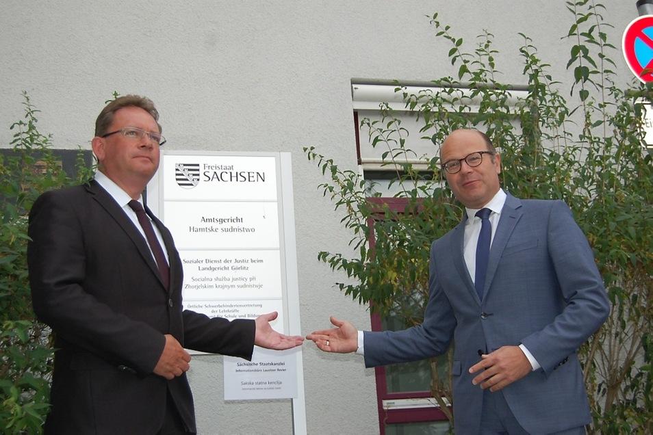 """Staatskanzleichef Oliver Schenk (rechts) und """"Botschafter"""" Bernhard Waldau brachten gestern das zunächst provisorische Büro-Schild an (unten)."""