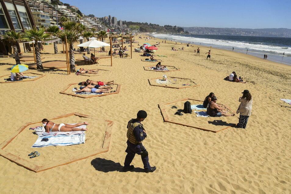 Daran werden wir uns wohl gewöhnen müssen: Ein Marinebeamter hält während der Ferienzeit am Strand von Renaca in Chile Wache. Am Strand wurden Bereiche markiert, damit die Besucher einen sicheren Abstand zueinander halten können.