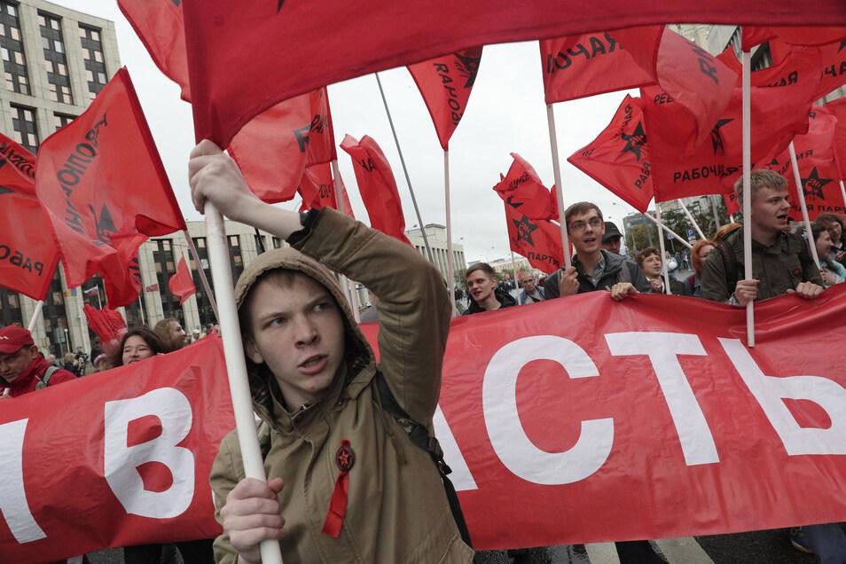 Unterstützer der Kommunistischen Partei schwenken rote Flaggen bei einem Protest. Demonstranten protestieren trotz eines erneuten Demonstrationsverbots in Moskau gegen den Ausschluss von Kandidaten zur Wahl zum Moskauer Stadtrat.