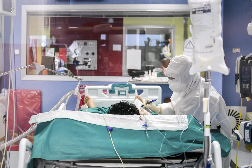 Ein medizinischer Mitarbeiter schreibt eine Notiz, um mit einem von ihm betreuten Patienten auf der Intensivstation des Bassini-Krankenhauses zu kommunizieren.