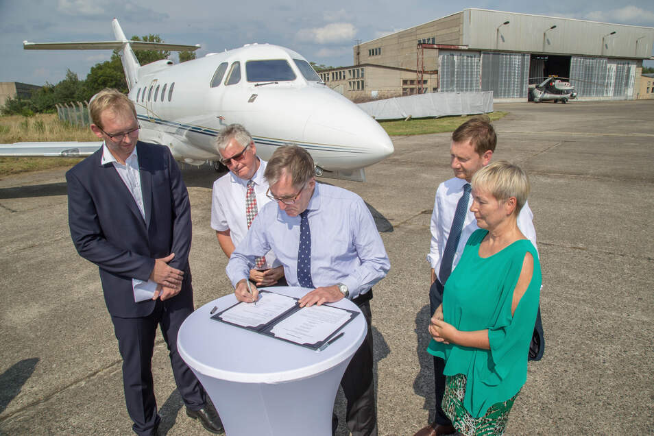 Andreas Sperl, Geschäftsführer der Elbe Flugzeugwerke, unterschreibt die Absichtserklärung zur Gründung eines Recyclingzentrums für Flugzeugteile und -materialien auf dem Rothenburger Flugplatz. Im Beisein von Ministerpräsident Michael Kretschmer und Bürg