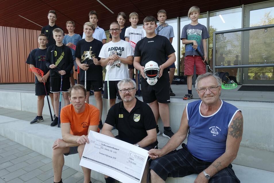 Karli Schubert (vorn rechts) und Rico Edenhofner (vorn links) von der Käferbande haben den Scheck an René Baier, Trainer der Ü 15-Mannschaft des UHC, übergeben.