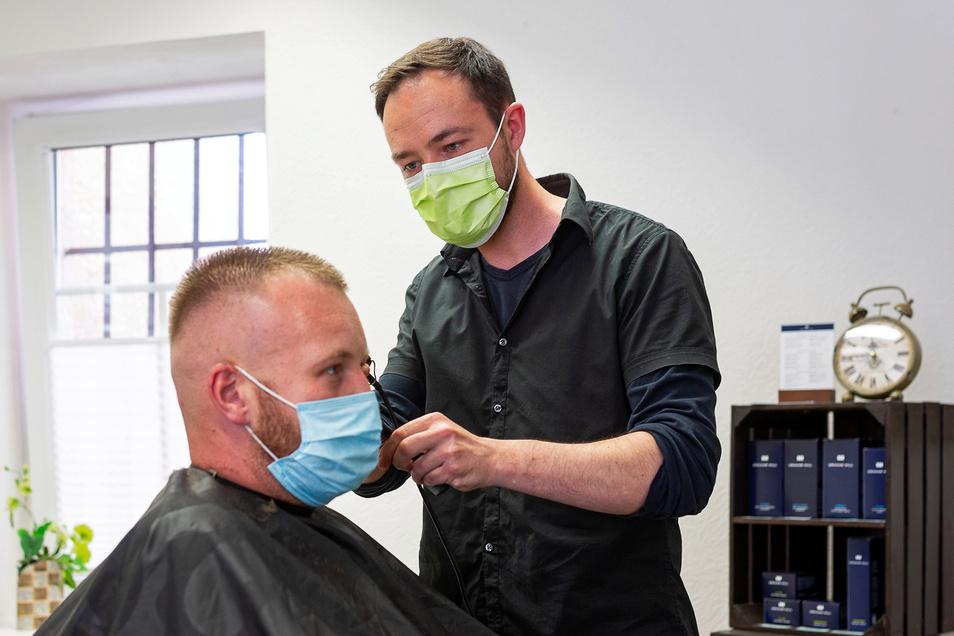 Derzeit nur mit Maske: Der Neustart im Salon Hein in Freital ist dennoch sehr gut angelaufen. Rechts: Geschäftsführer Friseurmeister David Walter, links ein Kunde.