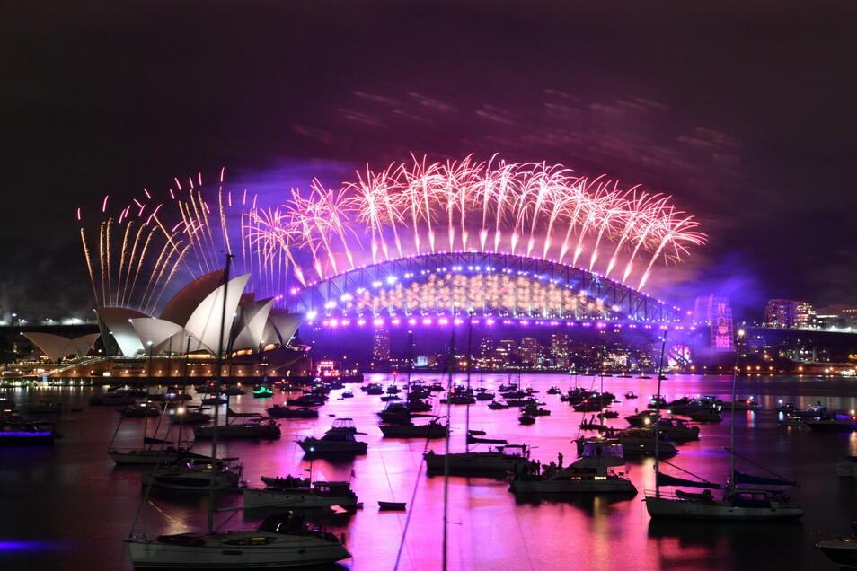 Australien, Sydney: Im Hafen treibende Boote werden vom Feuerwerk beleuchtet, das von der Sydney Harbour Bridge und dem Opernhaus (l) aus gestartet wird.
