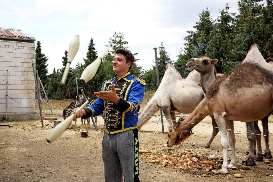 Adrian Schmidt jongliert im Freien, gleich neben dem abgesperrten Tiergelände.