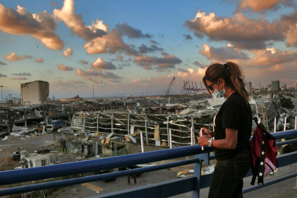 Eine libanesische Frau mit Mundschutz versucht, eine Kerze in der Nähe der Stelle anzuzünden, an der eine massive Explosion am Nachmittag des 04.08.2020 den Hafen von Beirut in die Luft sprengte.