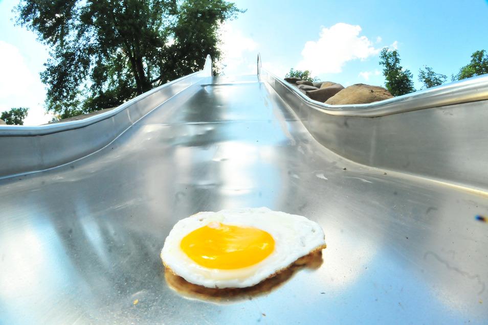 Die Metallrutsche am neuen Wasserspielplatz in Großenhain wird derzeit ganz schön heiß. Das Ei war zwar vorgebraten, allerdings backte es auf der Rutsche sofort an. Um die Mittagszeit ist die Rutsche nicht zu empfehlen.