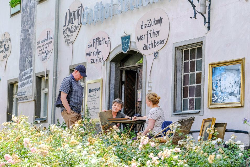 Susanne Martelock aus Weißenfels (Mitte) übergibt Kulturgeographin Juliane Vowinckel ein Gemälde an das Radebeuler Lügenmuseum.