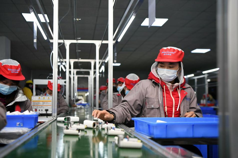 Menschen arbeiten in einer Fabrik am Fließband.