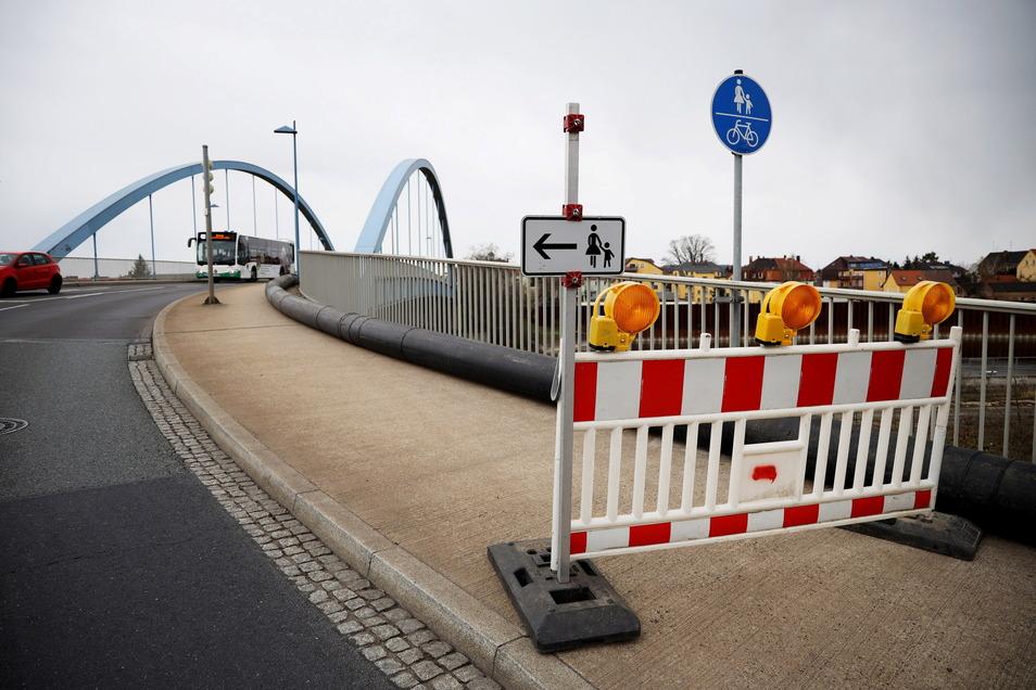 Der Fußweg auf der westlichen Seite der Riesaer Hafenbrücke ist aktuell gesperrt. Auf dem Gehweg liegt ein dickes, schwarzes Rohr. Hintergrund ist ein Vorhaben des Abwasserzweckverbands an der Kirchstraße.