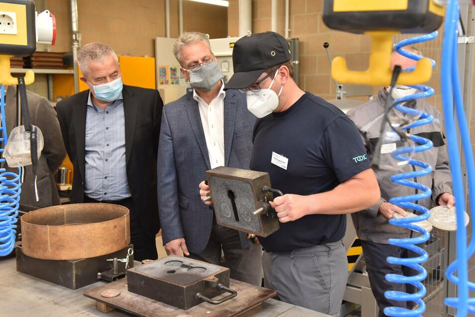 Azubi Tony Superzisnki erklärt Torsten Köhler, Geschäftsführer Bildung bei der IHK Dresden, und Landrat Michael Geisler (v.r.) die Funktion einer Gussform.