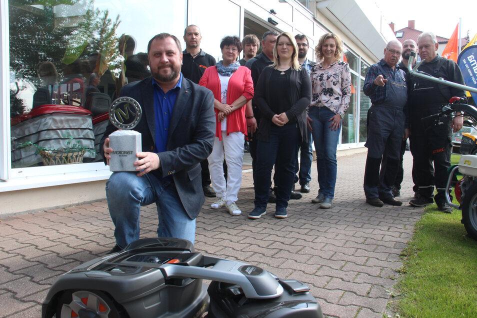 """Die Firma Gartentechnik Lehmann erhält die Auszeichnung """"Motorist des Jahres 2019"""" der gleichnamigen Fachzeitschrift. Im Vordergrund Firmenchef Lars Lehmann mit dem Pokal und einem Mähroboter der neuesten Generation."""