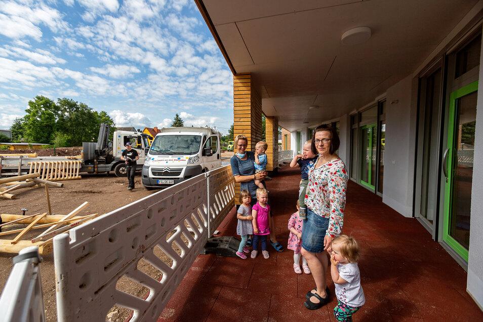 Leiterin Heike Holota (vorne) und Erzieherin Marion Lotze stehen hier mit den ersten sechs Kindern vor der neuen Krippe in Ruppendorf. Außen wird noch gebaut, innen ist alles fertig.