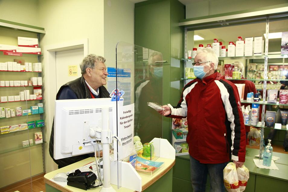 Der Görlitzer Apotheker Thomas Neumann händigt einem Kunden drei FFP2-Masken aus.