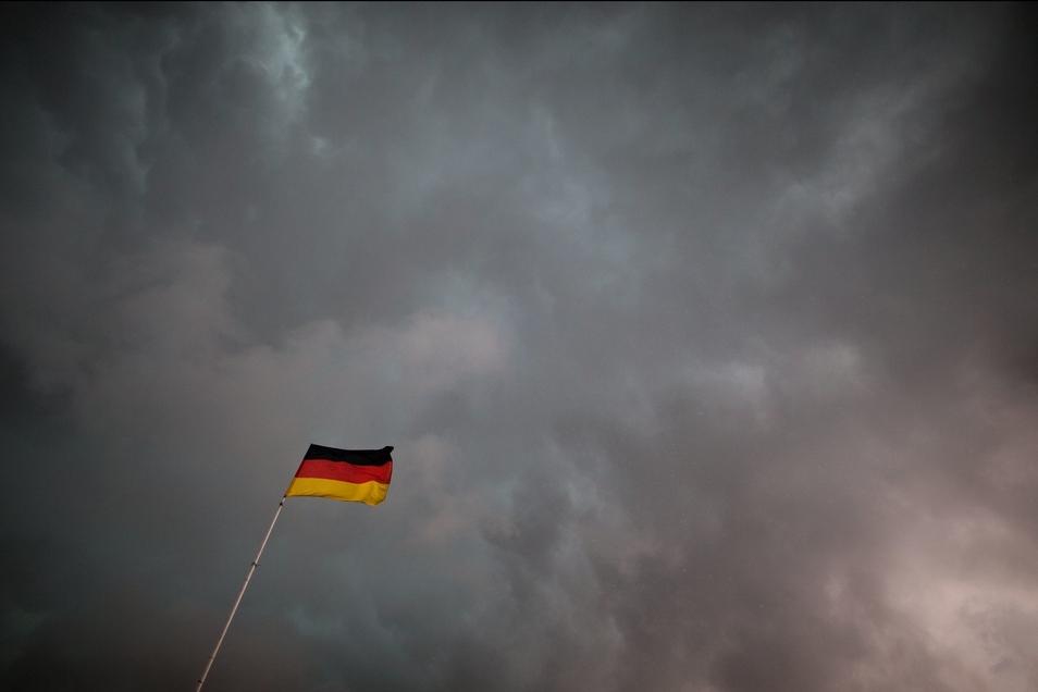 Neigen die Deutschen besonders zu Untergangsszenarien? Dunkle Wolken über der Nationalflagge.