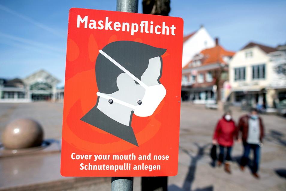 """Niedersachsen, Aurich: Ein Schild mit der Aufschrift """"Maskenpflicht"""" hängt auf dem Marktplatz. In Niedersachsen können die Bürger sogar darauf hoffen, dass sie nach Pfingsten ohne Maske einkaufen gehen dürfen."""