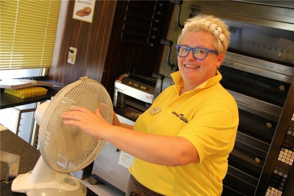 Claudia Mühlfeld von der Bäckerei-Filiale Möbius kühlt sich am Ventilator ab.