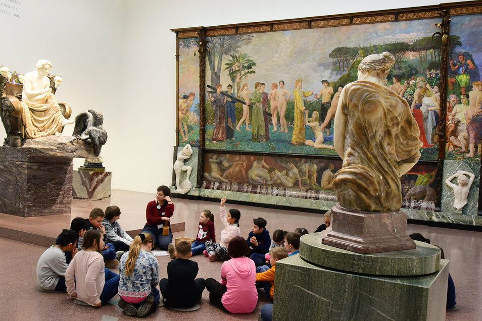 Eine 3. Klasse im Museum der bildenden Künste Leipzig. Die Kinder sitzen im Klingersaal und erfahren etwas über Max Klinger und über Ludwig van Beethoven, den Klinger in einer großen Figur (l.) verewigt hat.