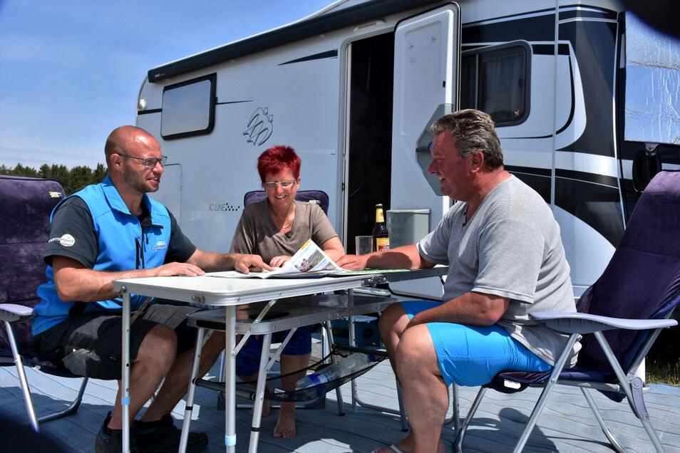 Lausitz statt Sardinien: Marco und Peggy Berthold aus Dresden haben sich am Geierswalder See gleich mal als Dauercamper angemeldet. Den Betreiber Martin Tinko (li.) freut's.