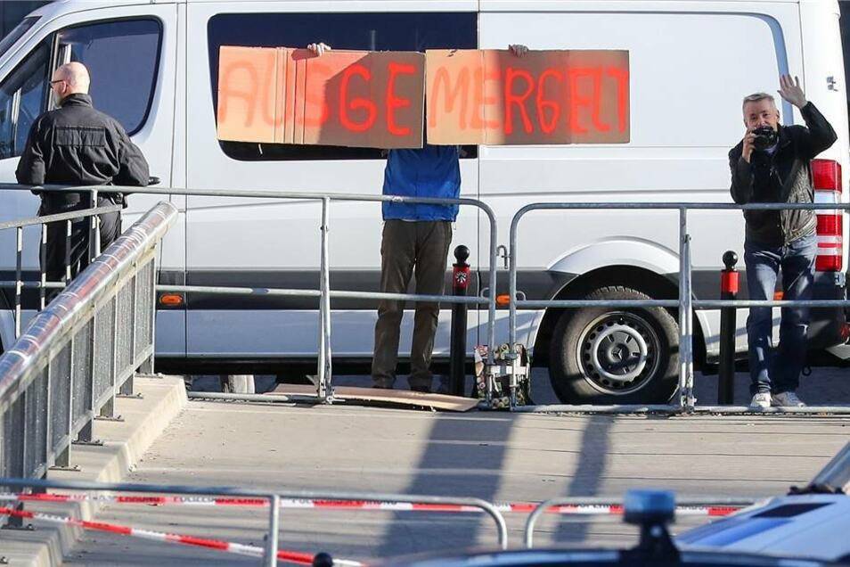 """Ein Mann hält ein selbstgemaltes Pappschild """"Ausgemergelt"""" hinter einer Polizeiabsperrung und den Dienstwagen der Kanzlerin vor der Hartmannhalle in Chemnitz in die Höhe."""