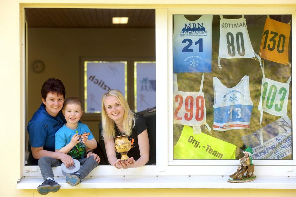 Aus Anlass des 90-jährigen Bestehens des Skiclubs Kottmar wird eine Ausstellung gestaltet. Miriam Krause (links) verwandelt die Fenster zu Ausstellungsflächen. Unterstützt wir sie von Schwiegertochter Gloria und Enkel Eddi.
