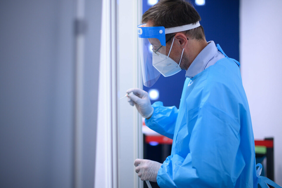 Ein Arzt der Kassenärztlichen Vereinigung Sachsen macht in der Corona-Teststation für Urlaubsrückkehrer am Flughafen Dresden einen Coronavirus-Test.