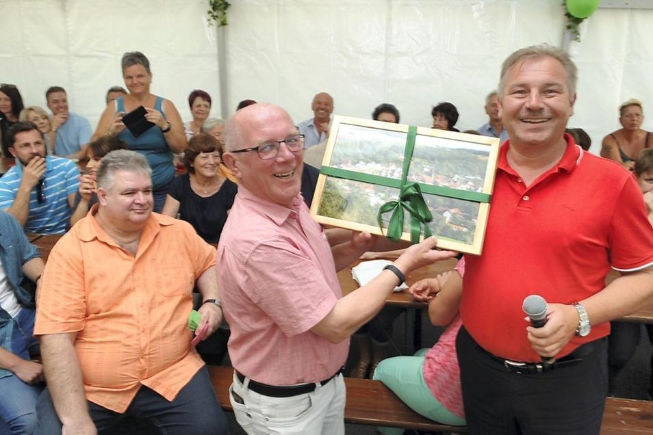 Bürgermeister Christian Krämer (rechts) übergibt ein Panorama-Foto der Partnergemeinde an den Bürgermeister von Nochten Achim Junker.