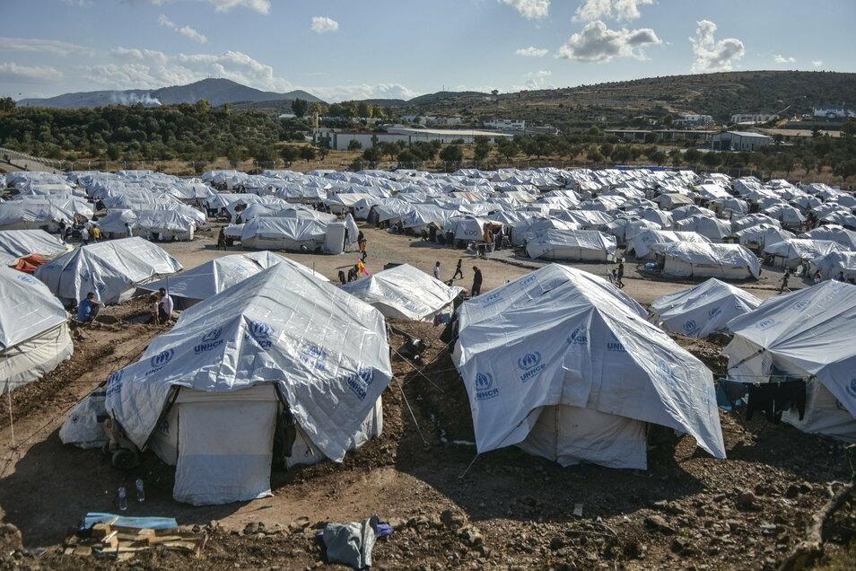 Griechenland, Lesbos: Migranten gehen nach einem starken Regenfällen durch das Flüchtlingslager Kara Tepe.