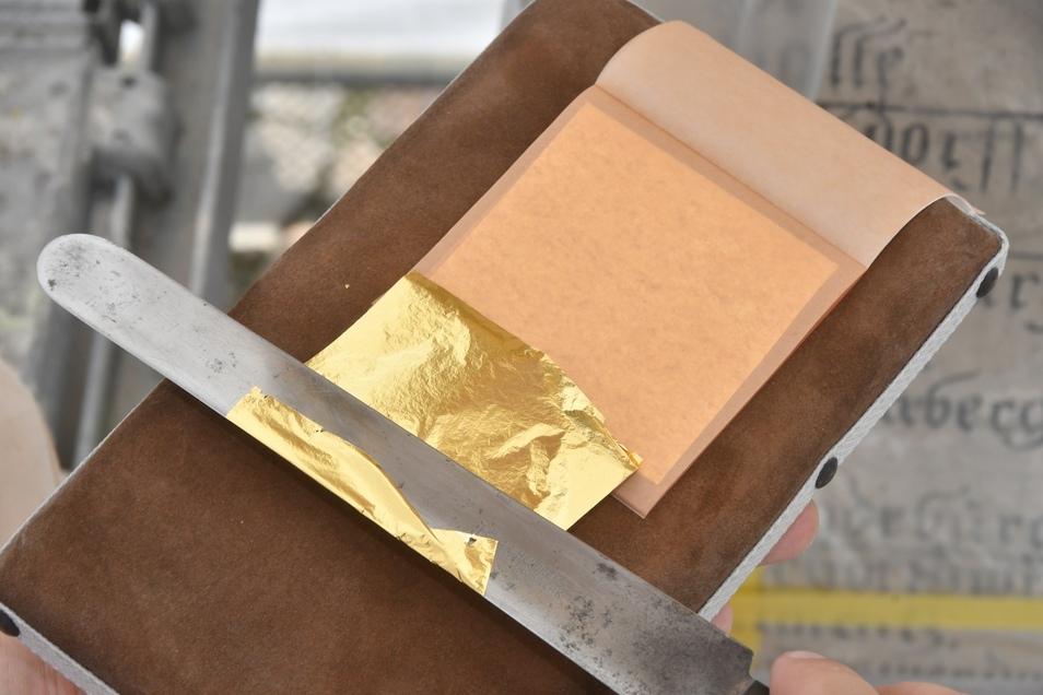 Das Blattgold wird mit einem Vergoldemesser aus dem Goldheftchen herausgehoben.