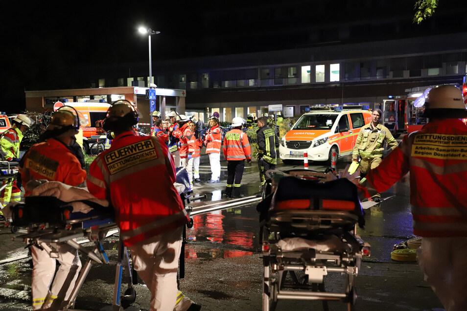 Feuerwehrleute und Krankentragen stehen nach einem Brand im Marien Hospital vor dem Krankenhaus um Patienten zu versorgen.