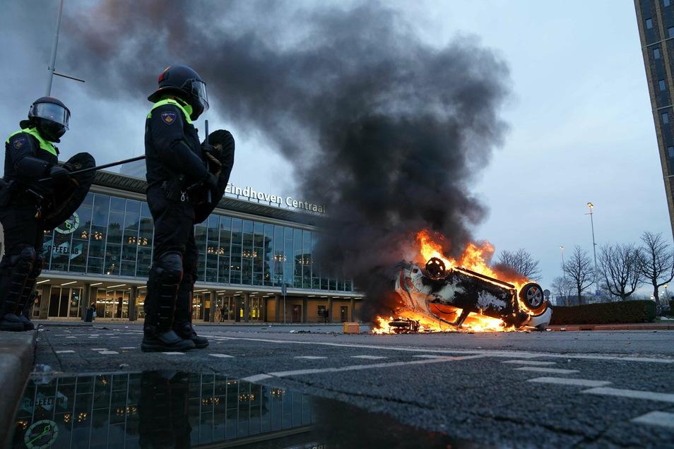 Flammen schlagen vor dem Bahnhof von Eindhoven aus einem umgekippten Auto